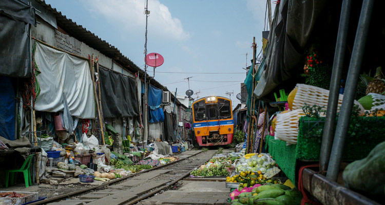 The train passes through market in Thailand